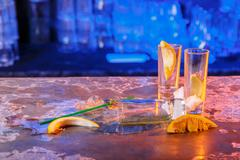 The spilled cocktails with ice cubes on blue color in the bar Stock Photos