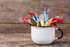 fishing baits wobblers protrude from white metal cup - stock photo