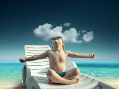 Child in sunglasses fun near the water - stock photo