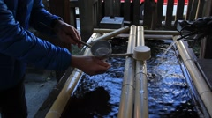 Man donating change to Japanese Shrine collection box Stock Footage