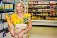 Smiling woman standing in aisle with grocery bag - stock photo