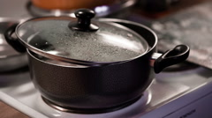 Dumplings are cooked in a saucepan with half closed lid - stock footage