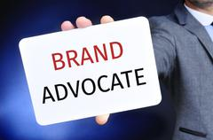 Businessman shows a signboard with the text brand advocate Stock Photos