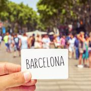 man at Las Ramblas shows a signboard with the word Barcelona - stock photo