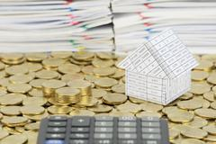 Pile of gold coins with house on stack gold coins - stock photo