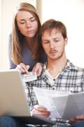 Serious Young Couple Looking At Home Finances - stock photo