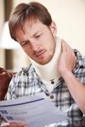 Man Wearing Surgical Collar Reading Letter - stock photo