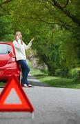 Female Motorist Broken Down On Side Of Road - stock photo