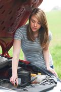 Broken Down Female Motorist Looking At Car Engine - stock photo