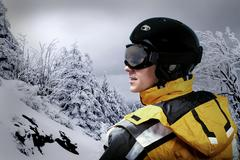 Portrait of man wearing a helmet and glasses on the background of snow winter - stock photo