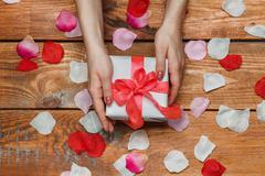 Valentines Day gift and Female hands on wooden background with petals - stock photo