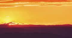 sunset scene with sun fall behind the mountains and clouds in background - stock footage