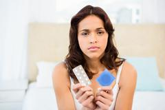 Concerned woman looking at contraception Stock Photos