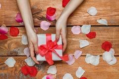 Valentines Day gift and Female hands on wooden background with petals Stock Photos