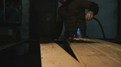 A carpenter in a workshop burns wood Stock Footage