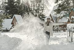 Smiling female funnig with snow at winter sunny day. - stock photo