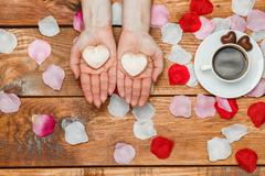 Stock Photo of Valentines Day concept.  Female hands with  hearts on wooden background