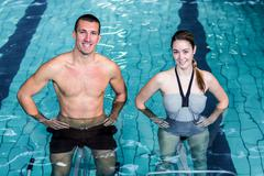 Smiling couple doing aqua aerobics Stock Photos