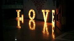 Word love consisting of lights on glossy floor - stock footage