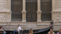 Two gondolas with tourists traveling on canal in Venice Stock Footage