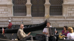 Tourists sitting down and listening to an accordion in a gondola, Venice Stock Footage