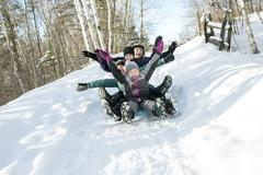Kids with parents is sledging in winter-landscape Stock Photos
