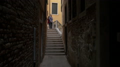 View of three people standing on a bridge with stairs in Venice Stock Footage