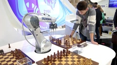 Visitors playing robot chess in game center Stock Footage