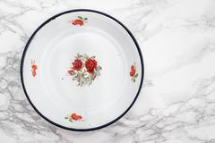 Empty White Vintage Enamel Plate with Flower Design - stock photo
