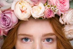 Closeup of beautiful woman eyes in flower wreath Stock Photos