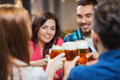 Stock Photo of friends drinking beer and clinking glasses at pub