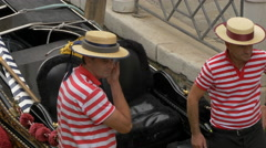 Gondolier with hat checking his wallet in Venice Stock Footage