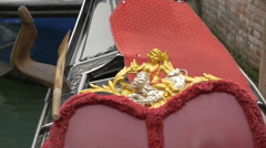 Golden child decoration on the red velvet seats of a gondola in Venice - stock footage