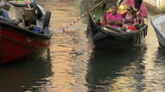 Two couples in two gondolas navigating near a moored boat in Venice Stock Footage