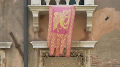 The Venetian coat of arms flag waving on a balcony in Venice Stock Footage
