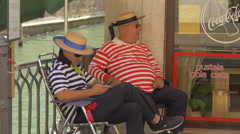 Two gondoliers sitting on a chair and talking in Venice Stock Footage