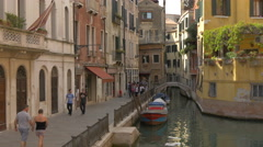 People walking on the shore and gondola navigating on a small canal in Venice Stock Footage
