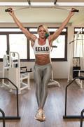 Woman Performing Hanging Leg Raises Abs Exercise - stock photo