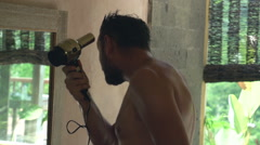 Young man drying his hair in bathroom, super slow motion 240fps Stock Footage