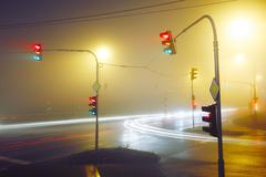 Traffic lights - crossroad in the foggy night - stock photo