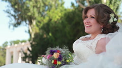 Bride sitting on the lawn with flowers - stock footage