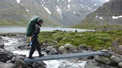 Trekker walking across a small bridge Stock Footage