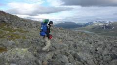 Trekker walking on big rocks, Jotunheimen Stock Footage