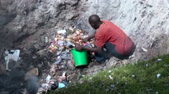 African informal garbage collector, in a fire hole to burn trash, gather garbage Stock Footage