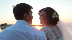 Newlyweds sitting at the berth near the lake at sunset - stock footage