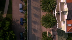 Aerial, vertical - Suburban street with palm trees and luxury apartments. Two ca Stock Footage