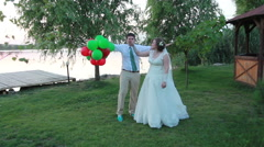 A couple of newlyweds are fooling around with balloons and danceing Stock Footage