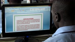 African student reading a computer network article at school using microsft word Stock Footage