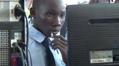 African student having a pen in his mouth while study in computer lab in school - stock footage