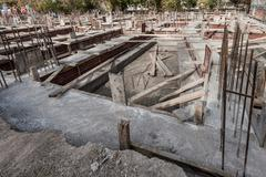 Foundation Site of New Building with Steel Bars and Cement - stock photo